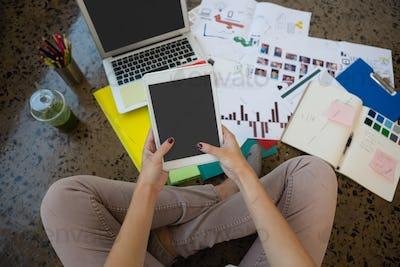 Woman using digital tablet sitting on floor at creative office