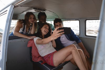 Front view of group of multi-ethnic friends taking a selfie in a camper van at beach