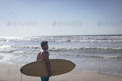 Side view of young Caucasian male surfer with a surfboard standing on beach on sunny day