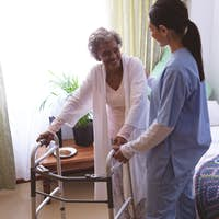 Female nurse helping senior female patient to stand with walker at nursing home
