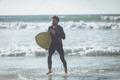 Male surfer with surfboard running out of the water