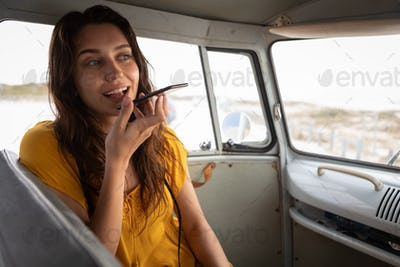 Woman talking on mobile phone in camper van at beach