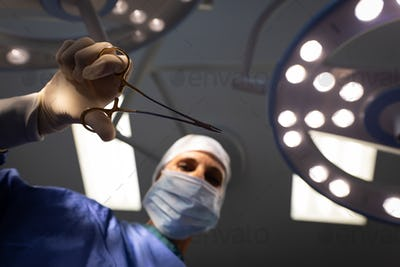 Female surgeon holding surgical scissors in her hand in operation theater
