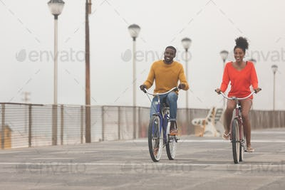 Front view of happy Multi-ethnic couple riding bicycle at promenade on a sunny day