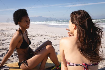 Women interacting with each other and smiling while sitting on the beach