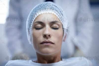 Front view of a Caucasian female patient sitting with eyes closed on bed at hospital