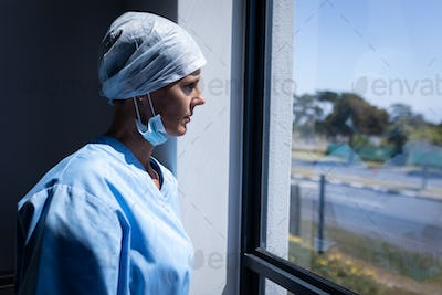 Side view of a Caucasian female surgeon looking through the window while standing in the hospital