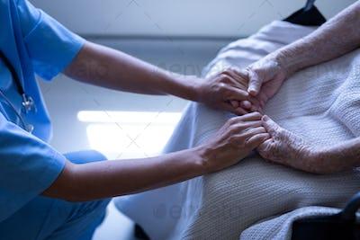 Female patient holding hands of surgeon in hospital corridor
