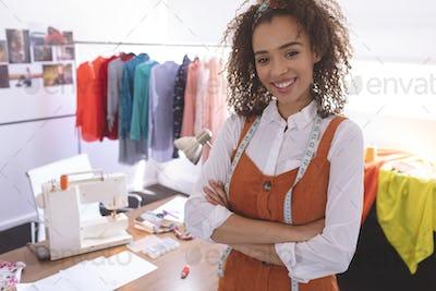 Female fashion designer standing at table in design studio