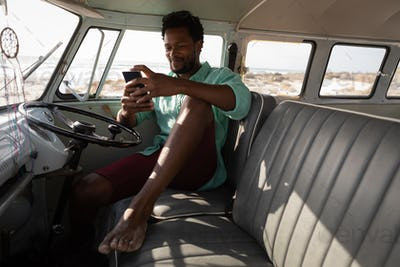 Front view of an African man sitting in a camper van while he is using his mobile phone at beach