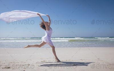 Side view of happy young Caucasian woman holding scarf at beach on a sunny day. She seems happy