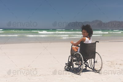 Woman disable sitting on wheelchair at beach
