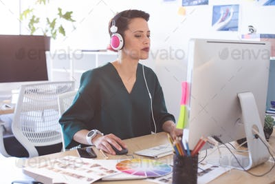 Side view of beautiful Mixed-race female graphic designer working on computer at desk in the office