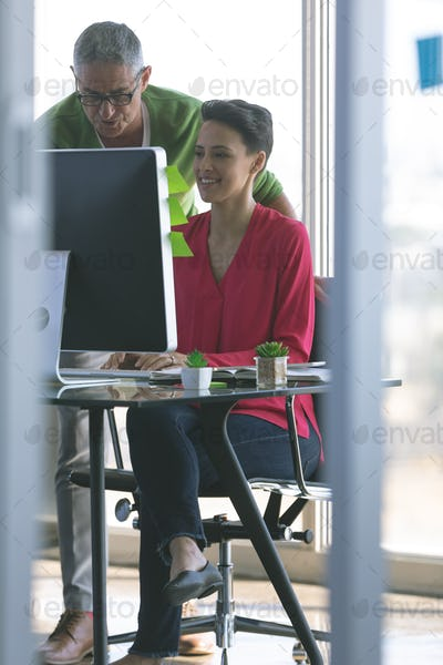 Front view of attentive Multi-ethnic business people working at desk in creative office