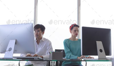 Front view of Multi-ethnic business people working on computer at desk in modern office