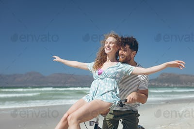 Side view of happy Caucasian couple enjoying on bicycle at beach on a sunny day. They are smiling