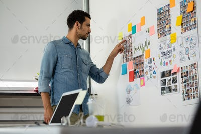 Side view of young attractive mixed race man pointing at photographs standing in creative office