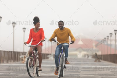 Front view of Multi-ethnic couple riding bicycle at promenade on a sunny day