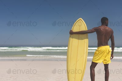 Rear view of African American male surfer with a surfboard standing on a beach on a sunny day