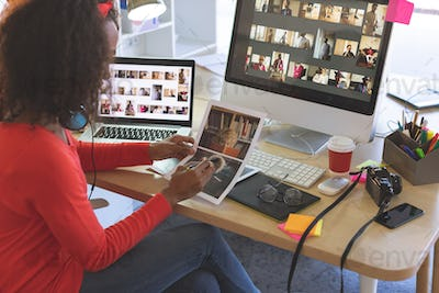 Side view of young mixed-race female graphic designer looking photographs at desk in a modern office