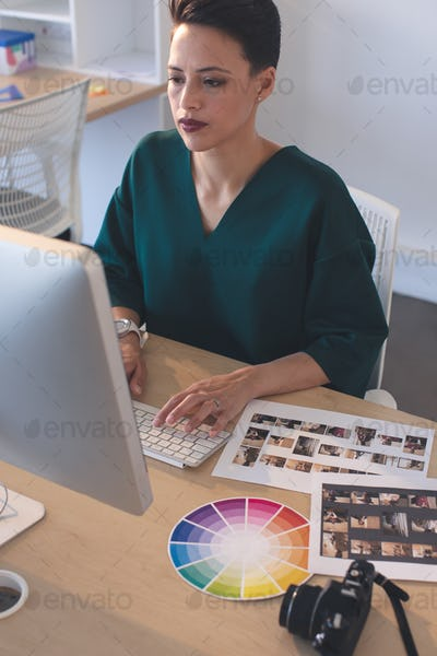 Female graphic designer working on computer at desk in the office