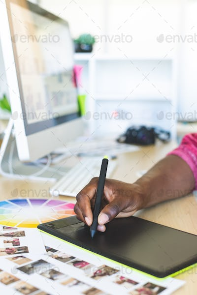 Close-up of young African-American graphic designer working on graphic tablet at desk in office