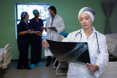 Female doctor looking at x-ray report in clinic at hospital