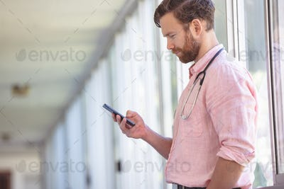 Side view of a  male Caucasian doctor using mobile phone while standing at nursing home corridor