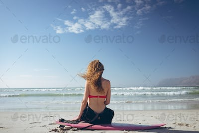 Female surfer sitting on surfboard face to the ocean at beach