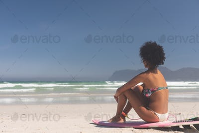 Side view of Mixed-race female surfer with a surfboard sitting on a beach. She is looking at the sea