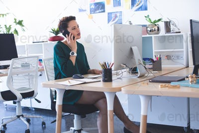 Side view of beautiful Mixed-race female executive talking on mobile phone at desk in the office