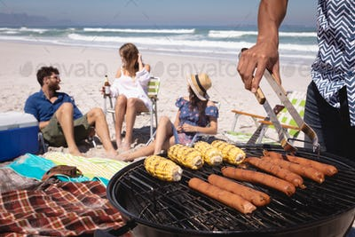 Mid-section of Mixed-race man doing a barbecue while his friends chilling at beach in background
