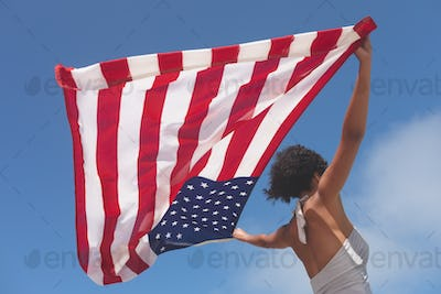 Low angle view of Mixed-race woman holding american flag that waves at beach