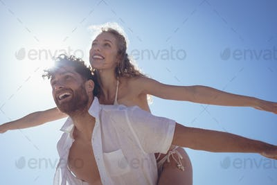 Young Caucasian man carrying pretty Caucasian woman piggyback at beach. They are smiling