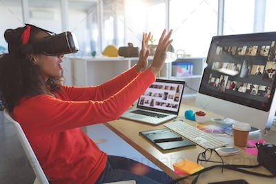Young female graphic designer using virtual reality headset at desk in a modern office