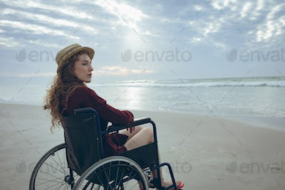Side view of young disabled Caucasian woman sitting on wheelchair at beach. She is looking away