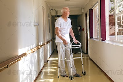 Side view of senior Caucasian male patient standing with walker in corridor at retirement home