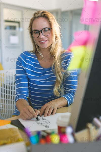 Young blonde female fashion designer looking and smiling at camera while drawing sketches at desk