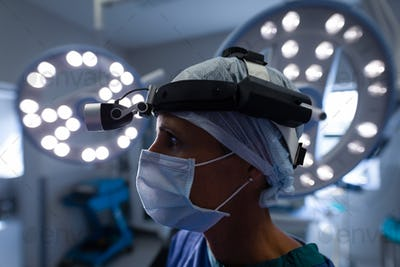 Female surgeon standing in operation theater and wearing an operation mask and a head lamp