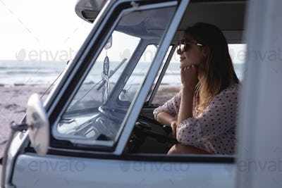 Side view of beautiful Caucasian woman sitting in camper van at beach on a sunny day