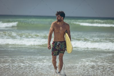 Front view of young Caucasian male surfer with a yellow surfboard walking at beach on a sunny day