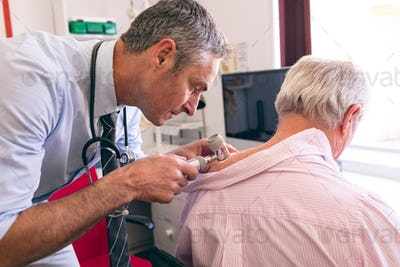 Mature male dermatologist examining senior patient with dermatoscopy at clinic at retirement