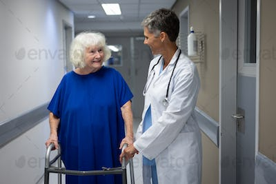 Mature female doctor talking with a senior Caucasian female patient in clinic at hospital
