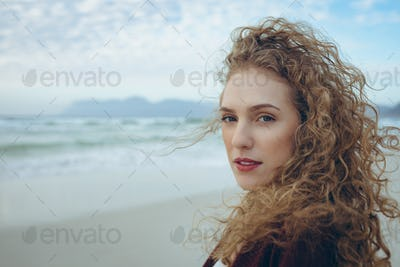 Portrait of beautiful young Caucasian woman looking at camera standing at beach.