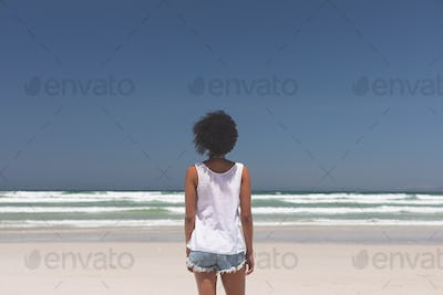 Rear view of beautiful young mixed-race woman standing at beach on a sunny day. She is looking ocean