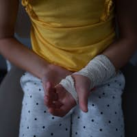Mid section of Caucasian girl sitting with fractured hand in clinic at hospital