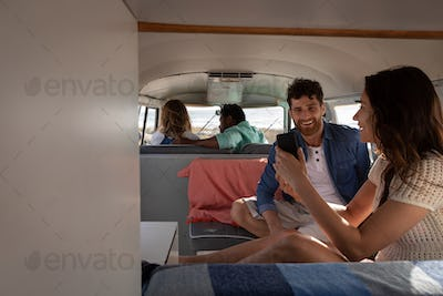 Group of multi-ethnic friends interacting with each others in camper van at beach on a sunny day