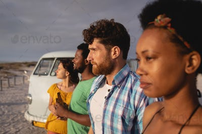 Friends group standing in raw on sand while they are looking away ocean against a camper van