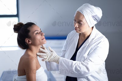 Side view of a mature mixed race female doctor checking the neck of a female patient in the clinic