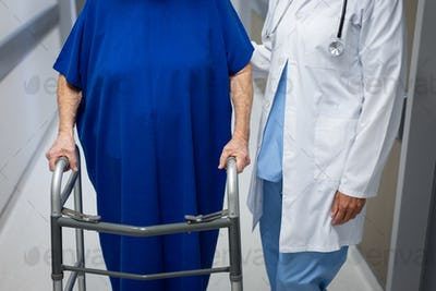 Mature female doctor and senior Caucasian female patient standing together in clinic